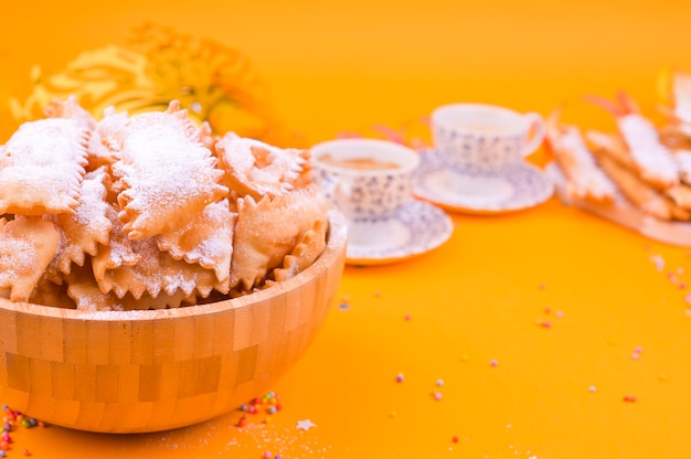 カーニバルマスク、2杯の芳香族コーヒー、お菓子、黄色の背景に紙吹雪。伝統的なイタリアの休日のための装飾。コピースペース。フラットレイ