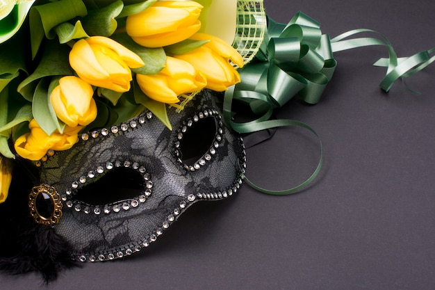 Carnival mask with a bouquet of yellow tulips.