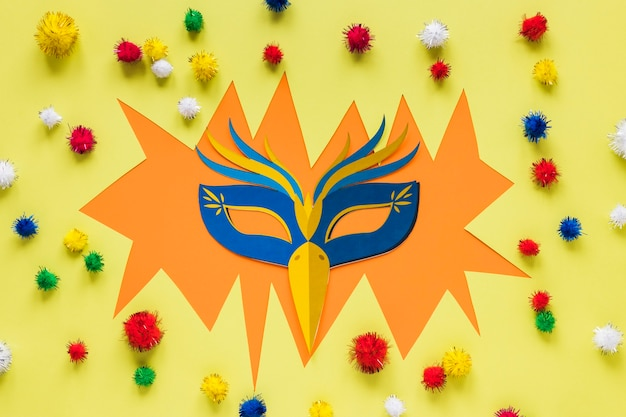 Carnival mask with colorful pom-poms