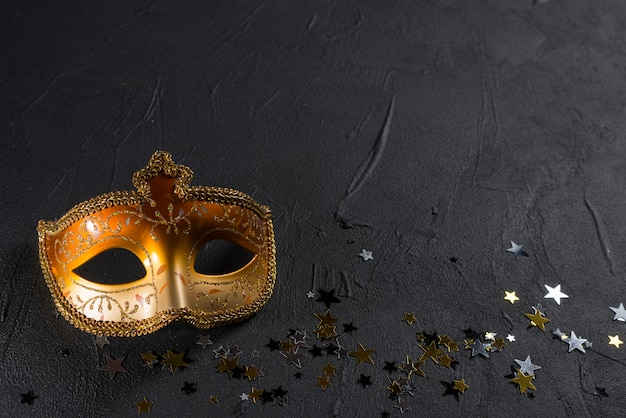 Carnival mask with spangles on black table