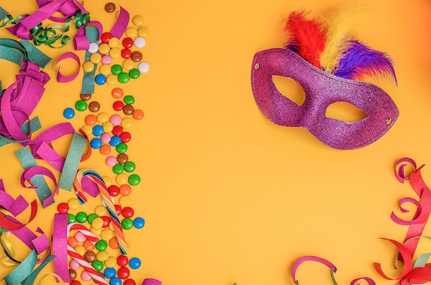 Carnival mask on a yellow background with mardi gras, brazilian, venetian carnival  with copy space