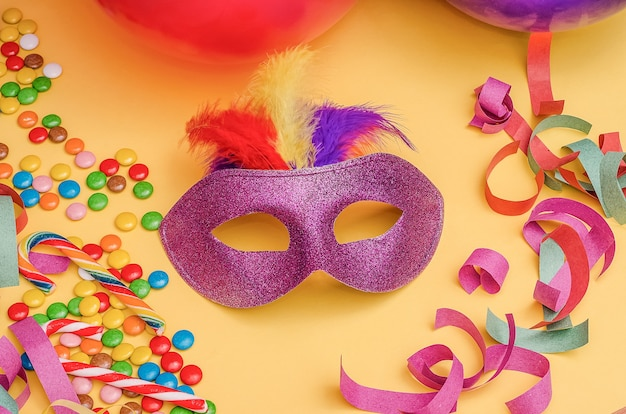 Carnival mask  on a yellow background with mardi gras, brazilian, venetian carnival