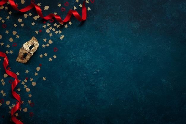 카니발 마스크와 골드 반짝이 색종이. 상위 뷰, 파란색 배경에 가까이