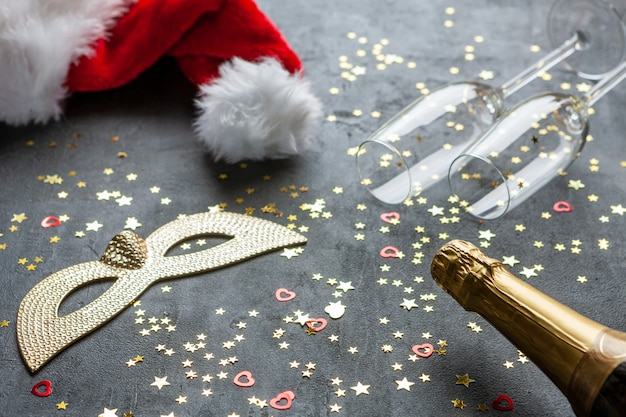 Carnival masks, champagne bottles, and santa claus red hat and two champagne glasses and gold glitter confetti,