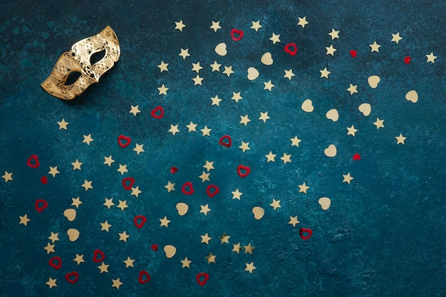 Carnival masks and gold glitter confetti. top view, close up on blue background