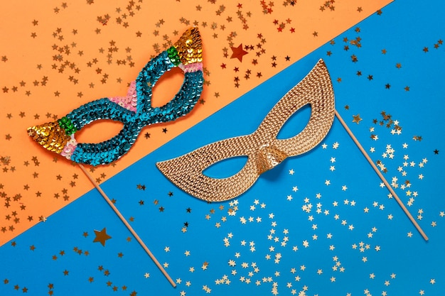 Carnival masquerade masks and gold glitter confetti. top view, close up on blue and orange colors background