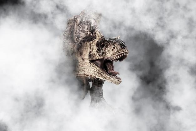 煙の背景にカルノタウルス恐竜