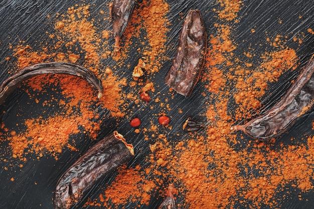 Carob chocolate and carob fruit powder on dark surface