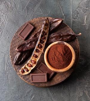 Порошок рожкового дерева и кладка крупного плана шоколада рожкового дерева плоская.