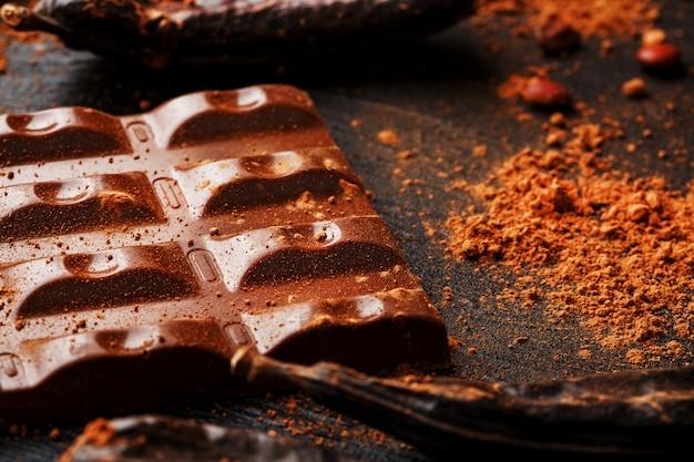 Carob шоколадный и фруктовый порошок рожкового дерева на темной поверхности