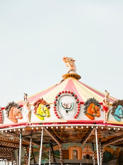 Carousel at amusement park against sky