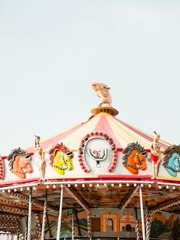 Carousel at amusement park against sky