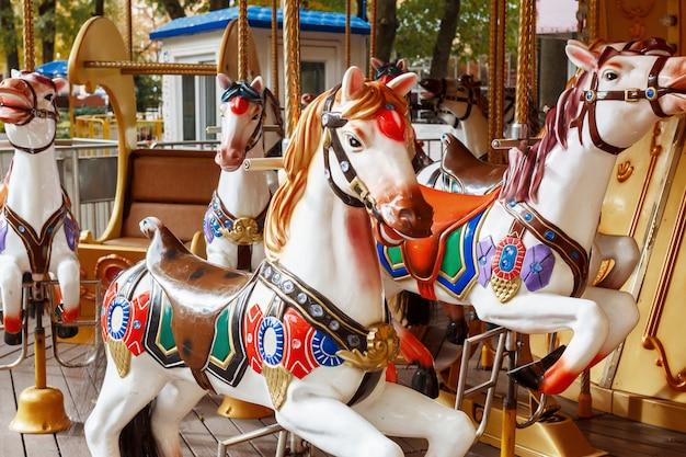 遊園地でカルーセル馬。アトラクションで馬のカルーセルのクローズアップ。
