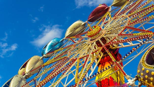 The carousel is spinning against the blue sky in amusement park, close-up