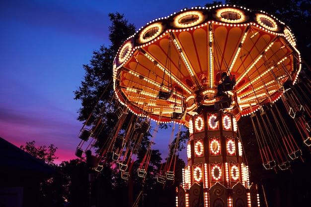 Карусель карусель в парке развлечений в вечернем городе