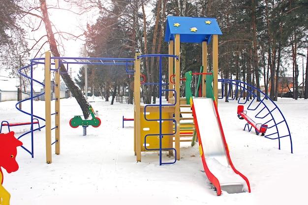 Карусель на детской площадке в зимнем лесу