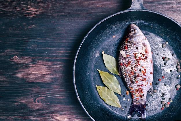 Carp fish in a black cast-iron frying pan