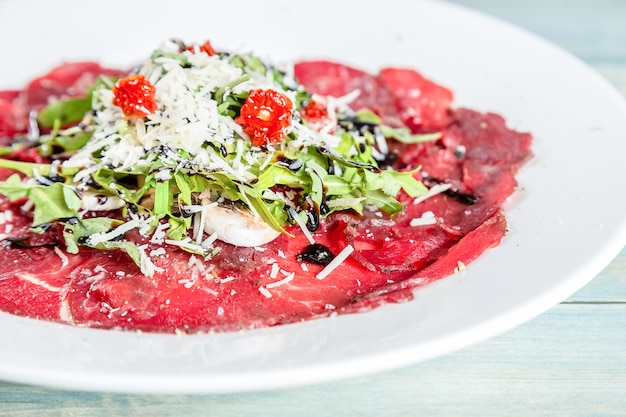 Carpaccio of beef with ruccola, parmesan cheese and dried tomatos