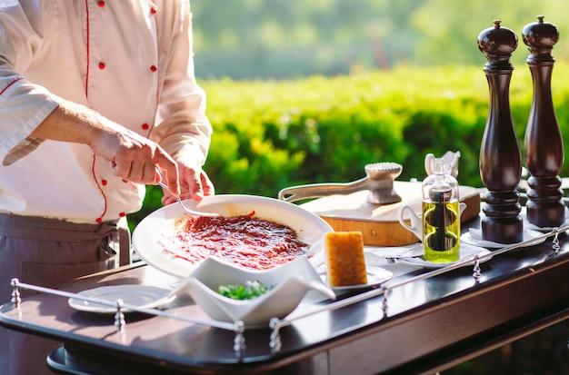 Показать кухню. повар готовит carpaccio family для гостей ресторана.