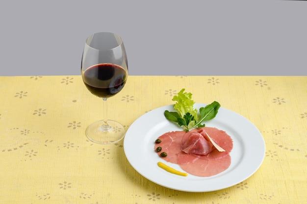 黄色のテーブルクロスの白い皿にカルパッチョ