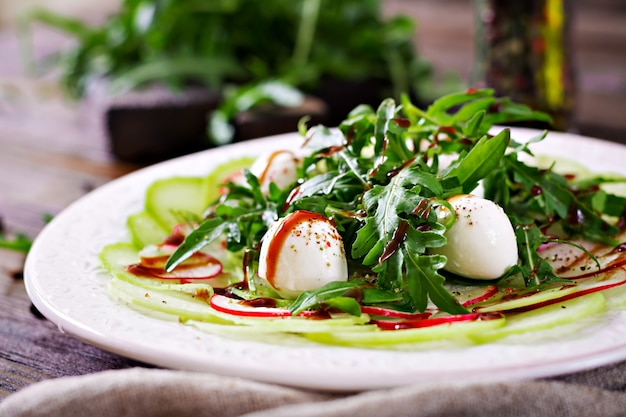 Carpaccio of radish with arugula, mozzarella and balsamic sauce. healthy food. daikon salad.