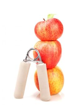 Кистевой эспандер и стопка из трех красных яблок