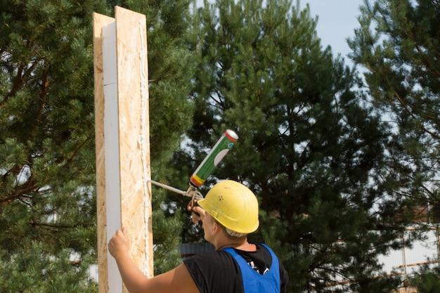 Плотник наносит столярный клей на деревянную изоляционную панель на строительной площадке для установки стен.