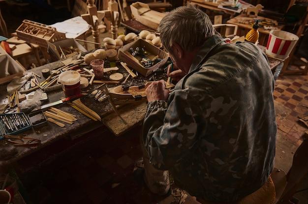 Плотник за работой. вид сзади старого мастера, делающего деревянную модель парусного корабля в своей домашней мастерской.