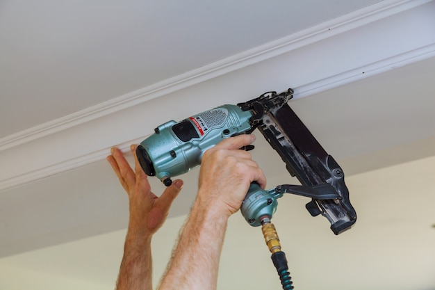 Carpenter brad using nail gun to crown moulding framing trim,