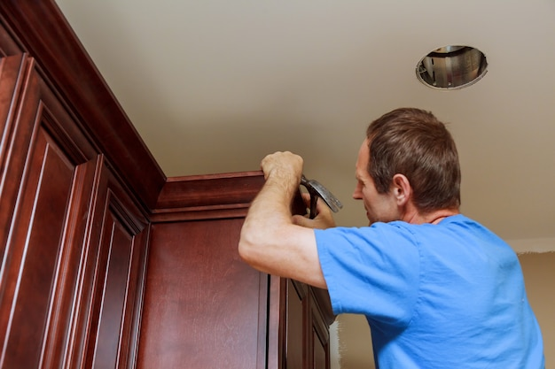 Carpenter brad using nail gun to crown moulding on kitchen cabinets framing trim,