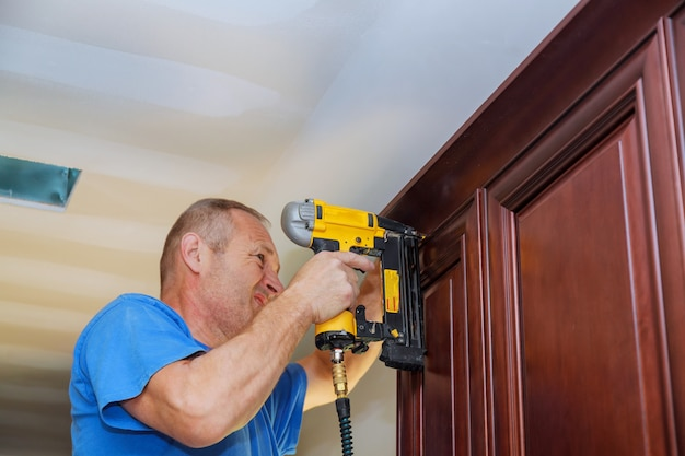 Carpenter brad using nail gun to crown moulding on kitchen cabinets framing trim