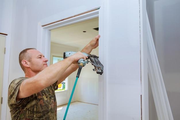 Carpenter brad using nail gun to moldings on doors,