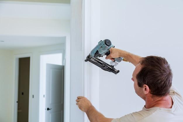 Carpenter brad using nail gun to moldings on doors