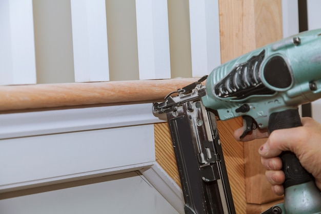 Carpenter brad using nail gun to moulding trim