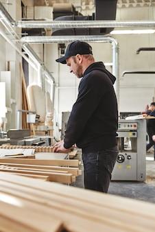 Карпентер проверяет свою работу столярные изделия и вид сбоку концепции мастерства