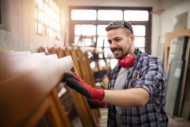 Плотник проверяет качество своей работы в столярной мастерской.