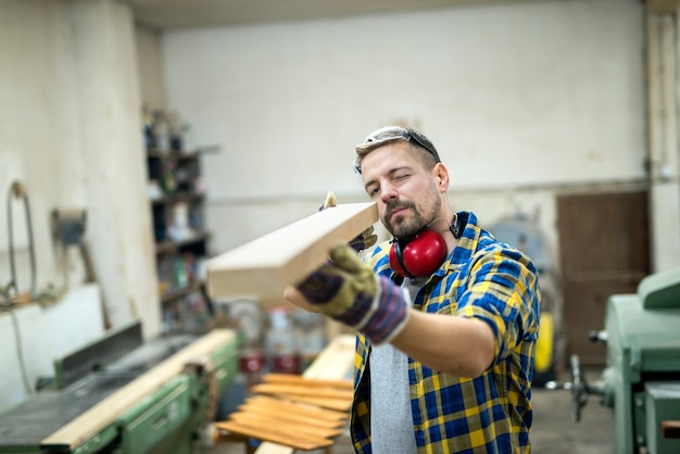 Carpenter checking quality of wood furniture part
