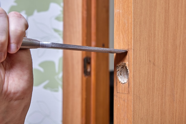 Carpenter cuts groove for door handle latch using chisel.