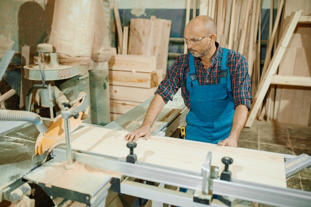 Carpenter cuts wooden board on circular saw machine, woodworking, lumber industry, carpentry.