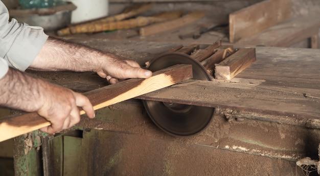 大工は木工機械で木片を切る。