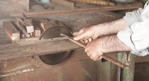 大工は大工機械で木片を切る。