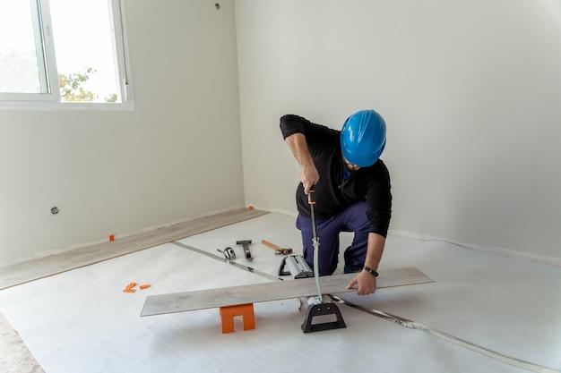 홈 리모델링에 바닥을 설치하기 위해 나무 한 장을 자르는 목수