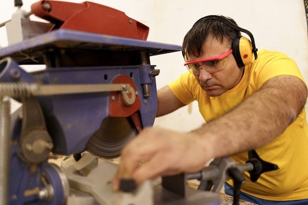 Carpenter cutting a piece of wood for furniture in his woodwork workshop, using a circular saw, and wearing safety goggles and earmuffs.