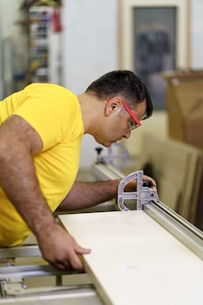 Carpenter cutting a piece of wood for furniture in his woodwork workshop, using a circular saw, and wearing safety goggles.
