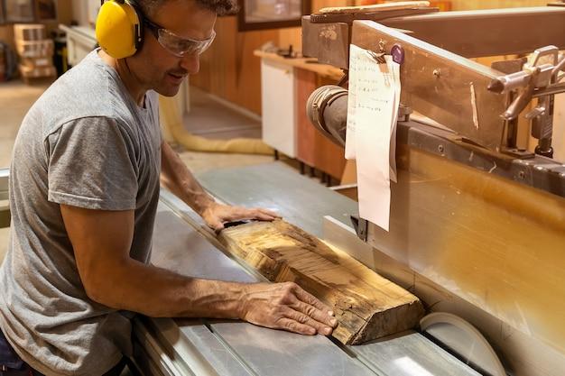 耳栓をつけた機械で木を切る大工。