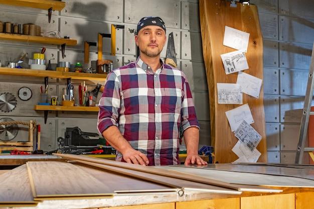 大工は大工仕事のワークショップで彼の仕事をしています。木工ワークショップの男がラミネートを測定し、カット