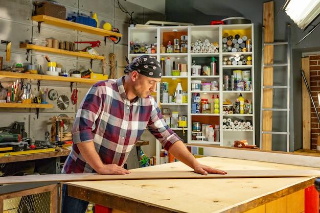 大工は大工のワークショップで彼の仕事をしています。大工仕事場の男がラミネートを測定してカットする