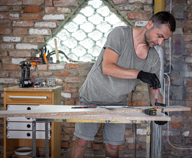 Carpenter doing wood work using clamping hand tool in his workshop.