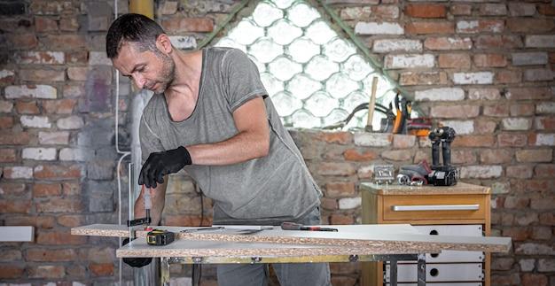 그의 작업장에서 클램핑 손 도구를 사용하여 목공 작업을 하는 목수.