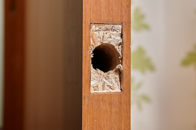 Carpenter drilled hole for latch of  door lock in chipboard sheet, and hollowed out rectangular frame with chisel to sink plate.